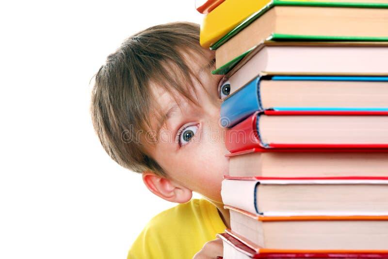 Förvånad unge bak böckerna arkivbilder
