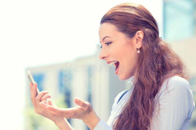 Förvånad upphetsad ung flicka som ser telefonen royaltyfri foto