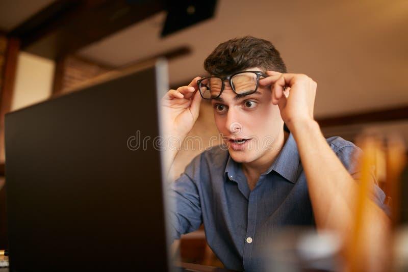 Förvånade blickar för freelancerhipsterman till bärbara datorn avskärmar och kan inte tro honom segrade visumet för det bända ell arkivbild