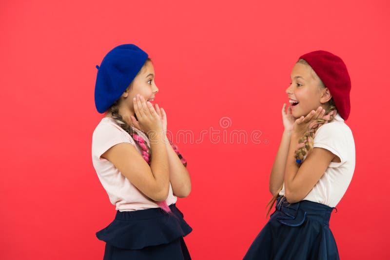 Förvånade flickor bär formell enhetlig röd bakgrund Internationellt utbytesskolaprogram Utbildning utomlands Applicera formen arkivbild