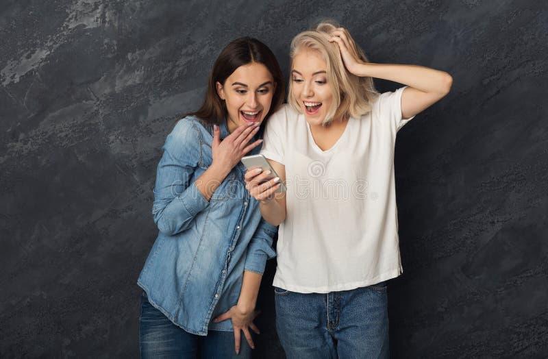 Förvånade kvinnliga vänner som använder smartphonen på den mörka studiobackgroen royaltyfria foton