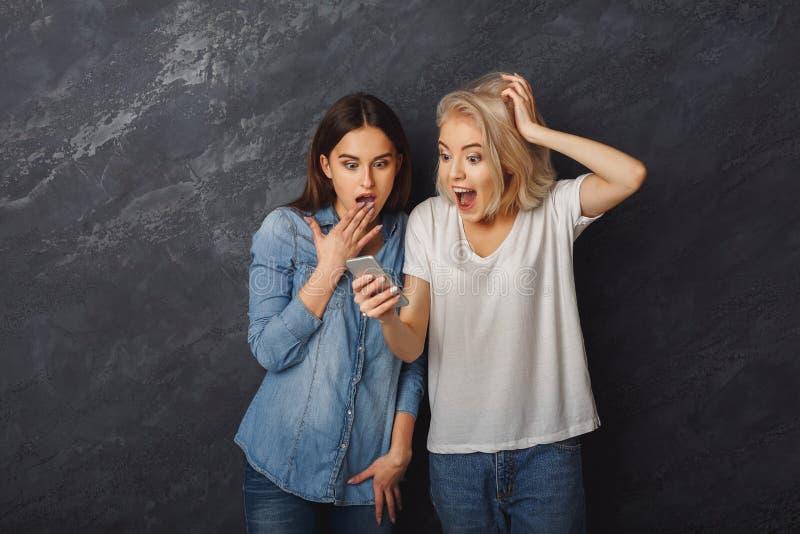 Förvånade kvinnliga vänner som använder smartphonen på mörk studiobakgrund royaltyfri foto