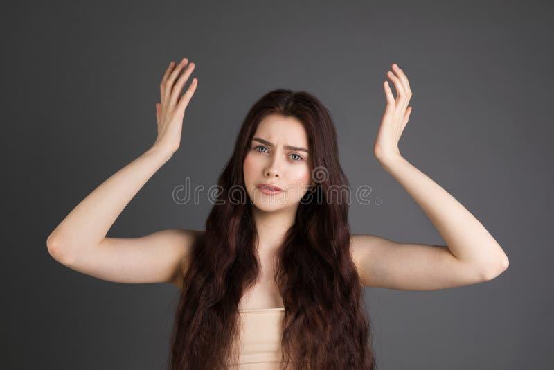 Förvånade livrädda kvinnliga gester med osäkert, förbryllat så vet inte svar på kuggfråga royaltyfria foton