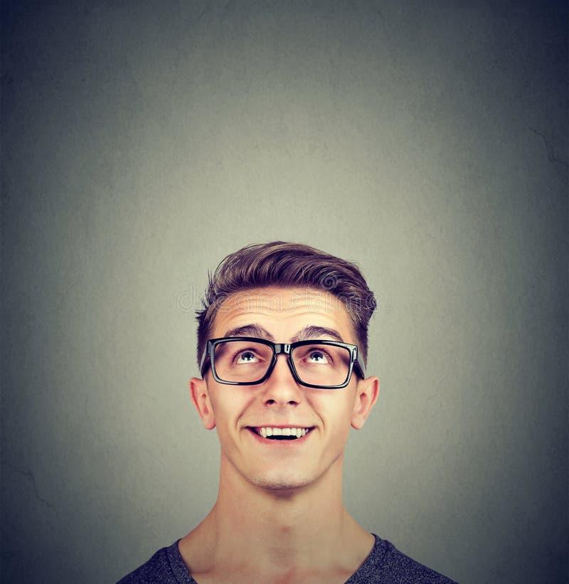 Förvånade lyckliga bärande exponeringsglas för ung man som ser upp arkivfoton