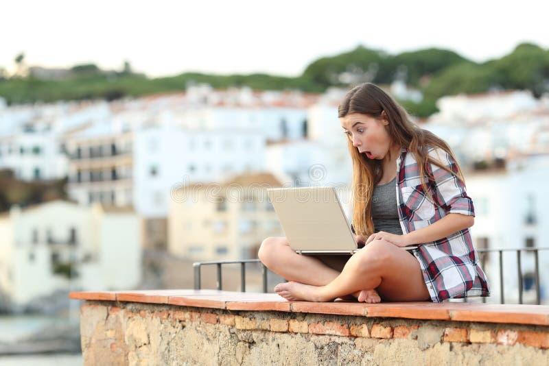 Förvånade tonåriga finna online-erbjudanden på en bärbar dator arkivbild