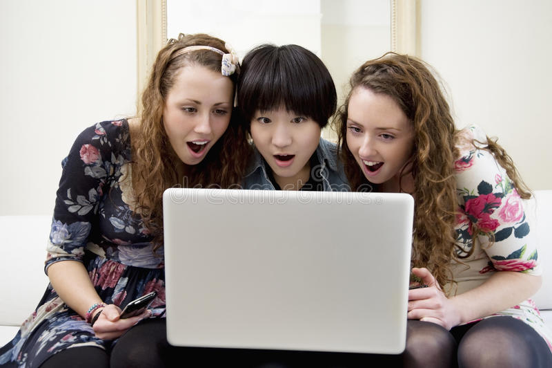 Förvånade vänner som ser något i bärbar dator royaltyfria foton