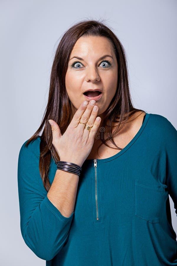Förvånadt mogna kvinnan som täcker henne munnen vid Hand royaltyfri bild