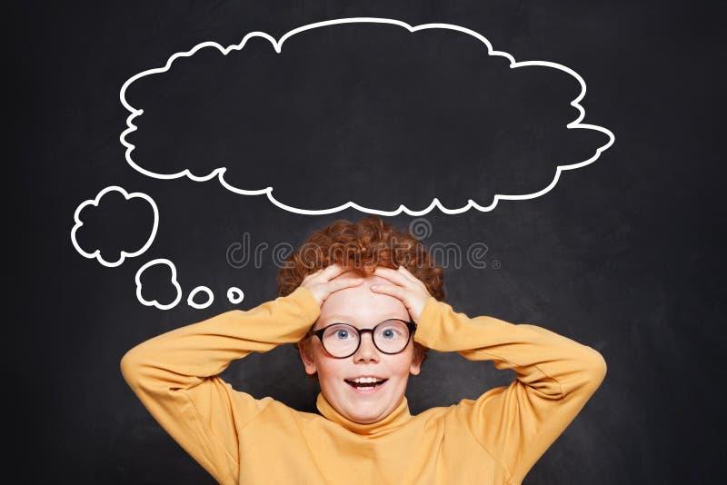 Förvånat barn med den stora tomma anförandemolnbubblan på svart tavlabakgrund royaltyfri fotografi