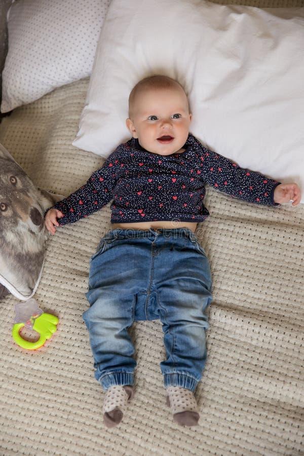 Förvånat behandla som ett barn flickan som ligger på säng och ser upp royaltyfri fotografi