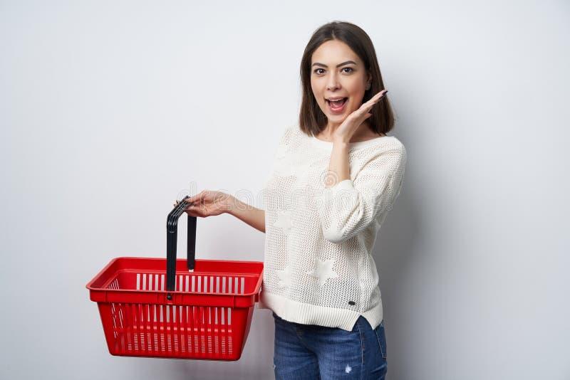 Förvånat brunettkvinnaanseende av den vita väggen som rymmer den tomma shoppa korgen royaltyfria foton