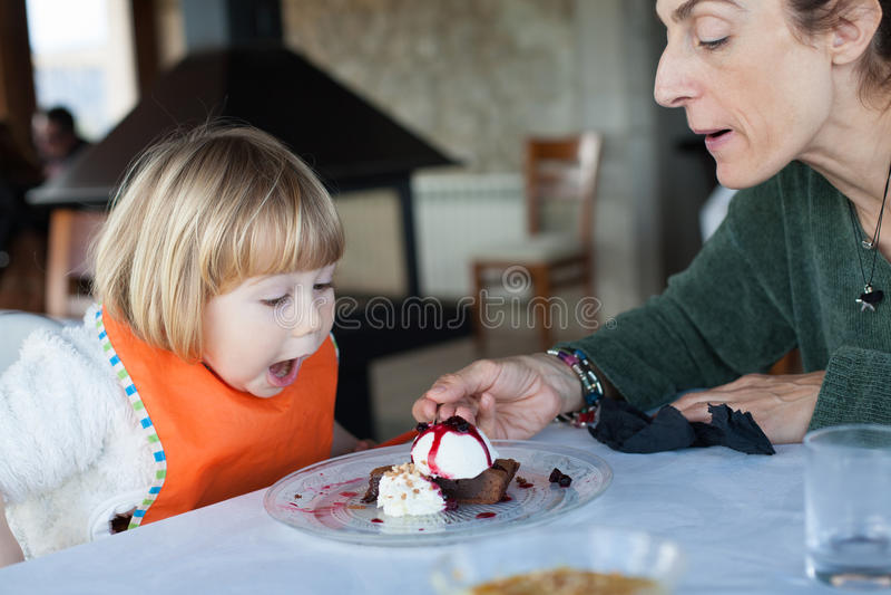 Förvånat framsidabarn som äter kakan med modern fotografering för bildbyråer