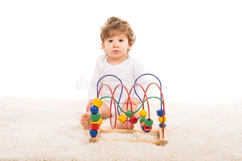 Förvånat litet barn med träleksaken arkivbild