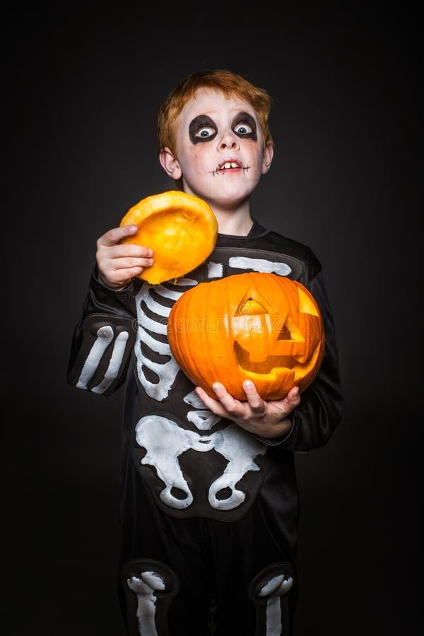 Förvånat rött haired barn i den skelett- dräkten som rymmer en orange pumpa halloween royaltyfria foton