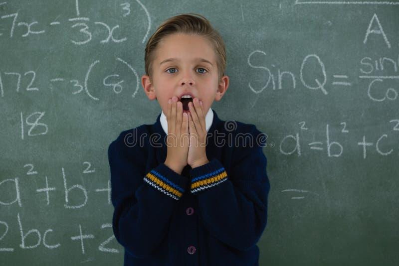 Förvånat skolpojkeanseende mot den svart tavlan royaltyfri foto