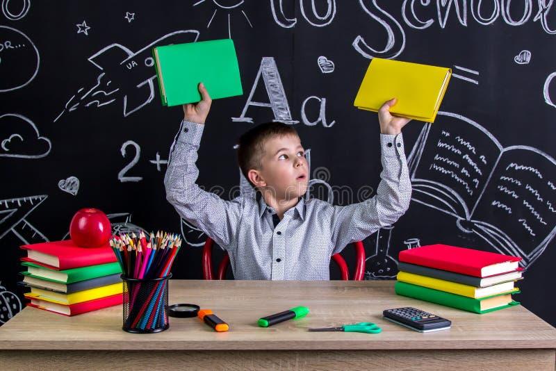 Förvånat skolpojkesammanträde på skrivbordet med böcker, skolatillförsel, hållande upp två böcker i hans båda armar som ser arkivfoton