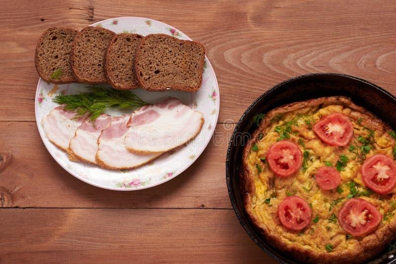 Förvanskad ägg och bacon på en trätabell royaltyfria bilder