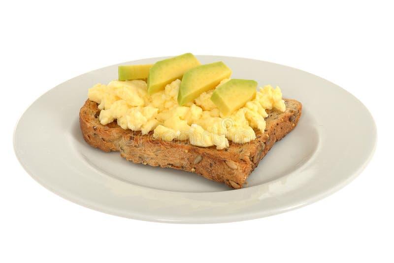 Förvanskad äggfrukost på Wholemealrostat bröd med avokadot royaltyfria bilder