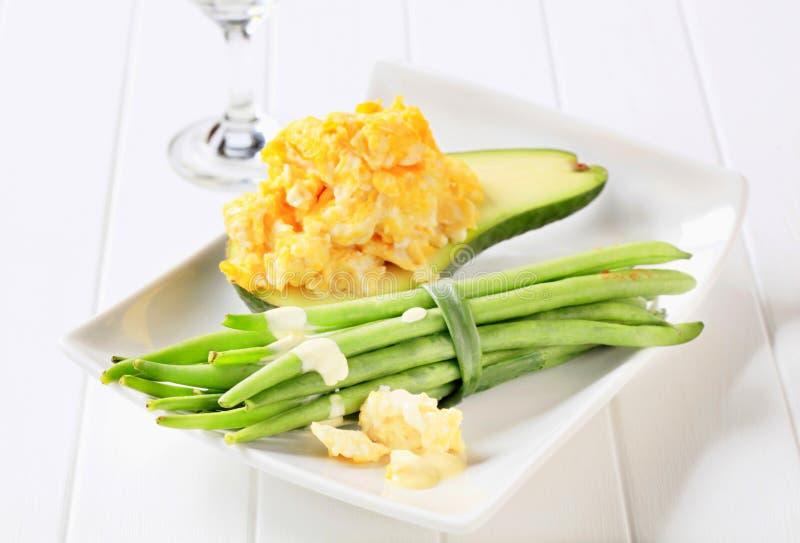 Förvanskade ägg med avokadot och haricot vert arkivfoton