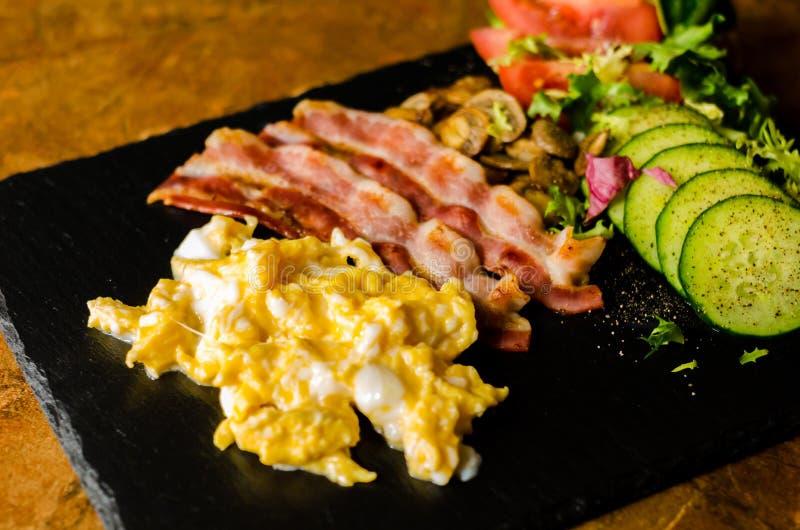 Förvanskade ägg med bacon, champinjoner tjänade som med sallad, tomat a arkivbild