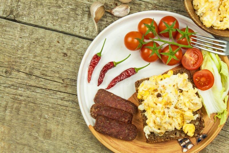 Förvanskade ägg med bröd och salami Äggfrukost på en trätabell sund mat royaltyfri bild