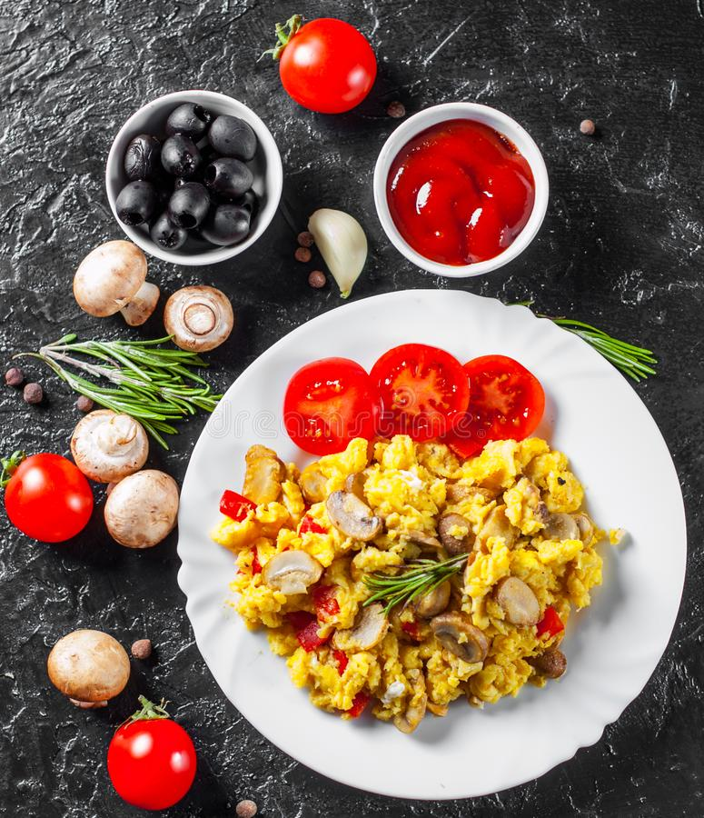Förvanskade ägg med champinjoner och grönsaker i den vita plattan royaltyfri bild
