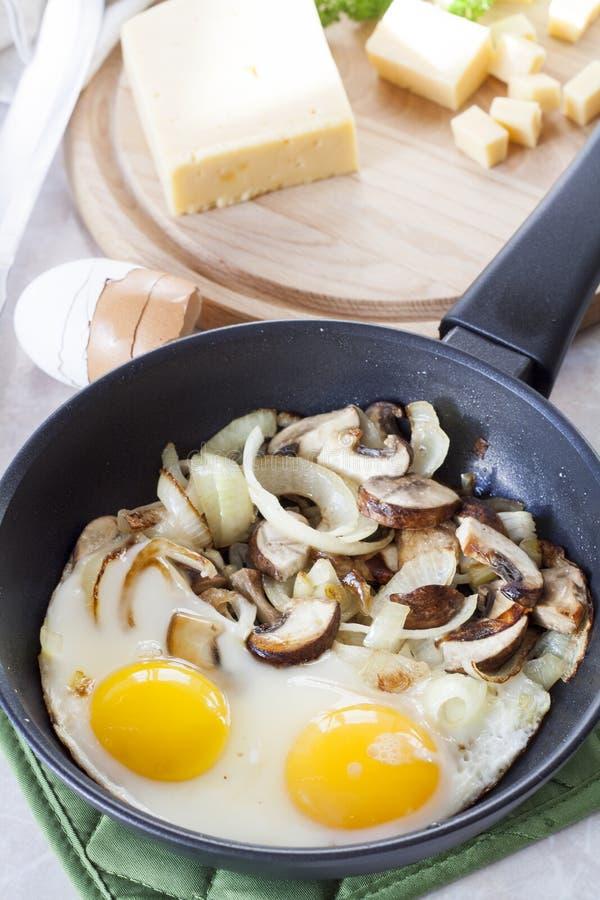Förvanskade ägg med champinjoner till stekpannan, skivad ost och örter arkivbild