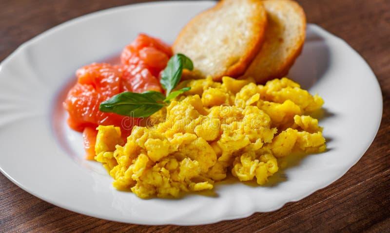 Förvanskade ägg med den rökte laxen och rostat bröd i den vita plattan på trätabellen royaltyfri foto
