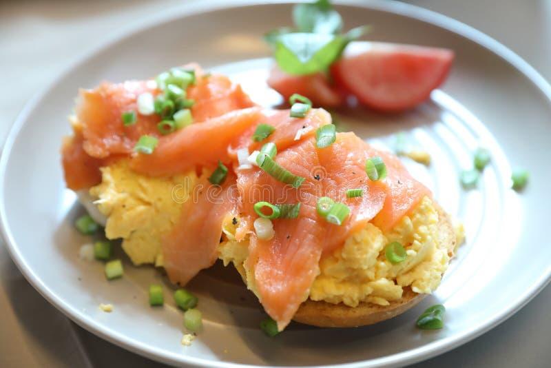 Förvanskade ägg med den rökte laxen på rostat bröd, frukostmat arkivbild
