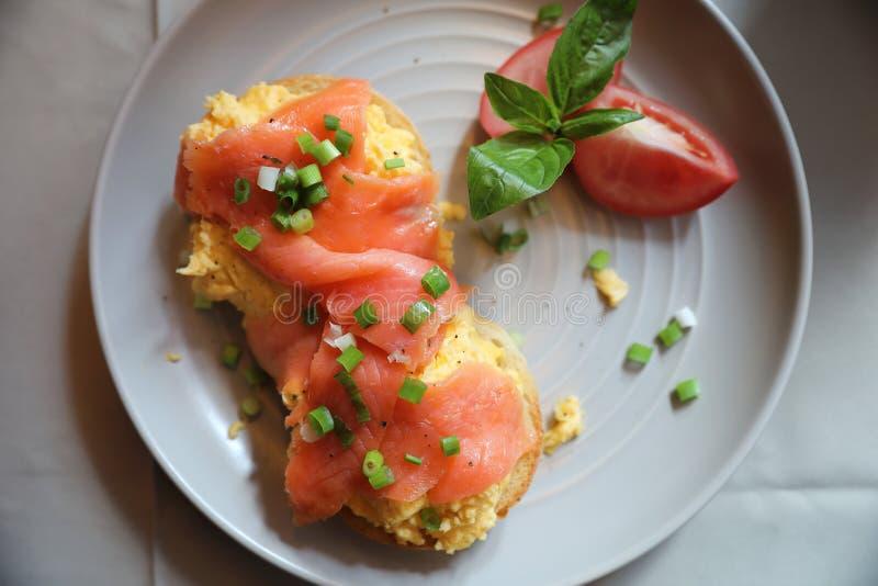 Förvanskade ägg med den rökte laxen på rostat bröd, frukostmat royaltyfria bilder