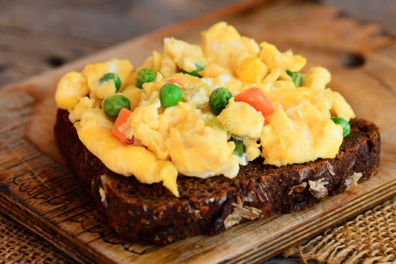Förvanskade ägg med grönsaker på rågbröd Mjuk förvanskad äggomelett Hemlagad kokkonst lantlig stätta closeup royaltyfria bilder
