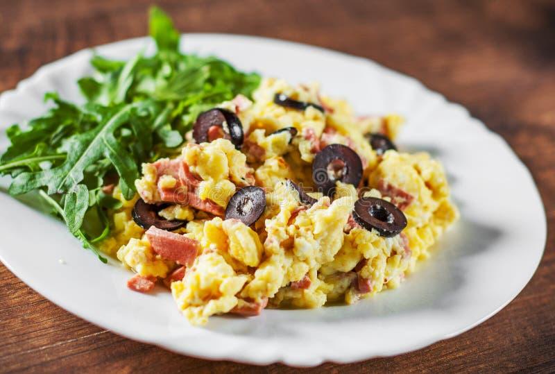 Förvanskade ägg med skinka-, oliv- och arugulasallad i den vita plattan på trätabellen arkivfoto
