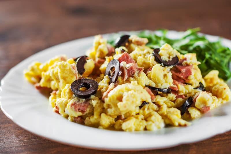 Förvanskade ägg med skinka-, oliv- och arugulasallad i den vita plattan på trätabellen royaltyfria bilder