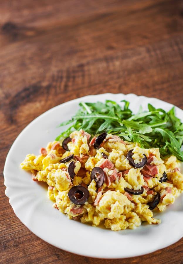 Förvanskade ägg med skinka-, oliv- och arugulasallad i den vita plattan på trätabellen arkivbilder