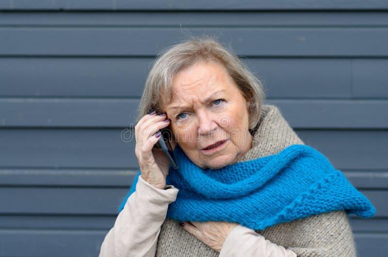 Förvirrad äldre kvinna som pratar på hennes mobil royaltyfria bilder