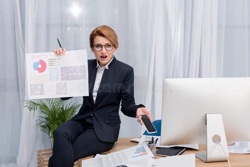 förvirrad affärskvinna med dokumentet och smartphone på arbetsplatsen royaltyfri bild