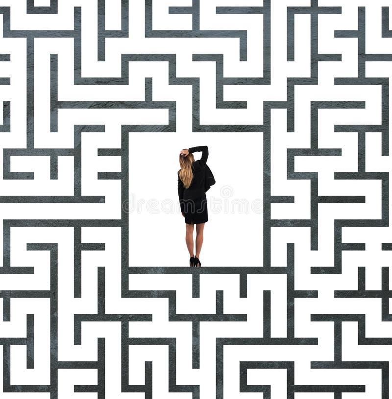 Förvirrad affärskvinna på mitten av en labyrint royaltyfri fotografi