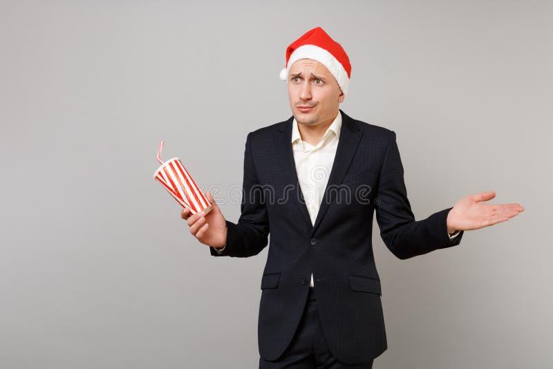 Förvirrad affärsman i plast- kopp för julhatthåll av den fördelande handen för cola som isoleras på grå bakgrund arkivfoto