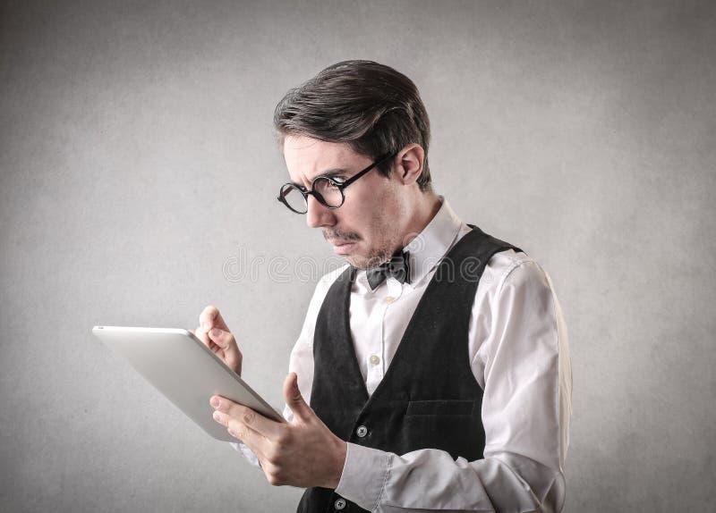 Förvirrad affärsman som använder en minnestavla arkivfoto