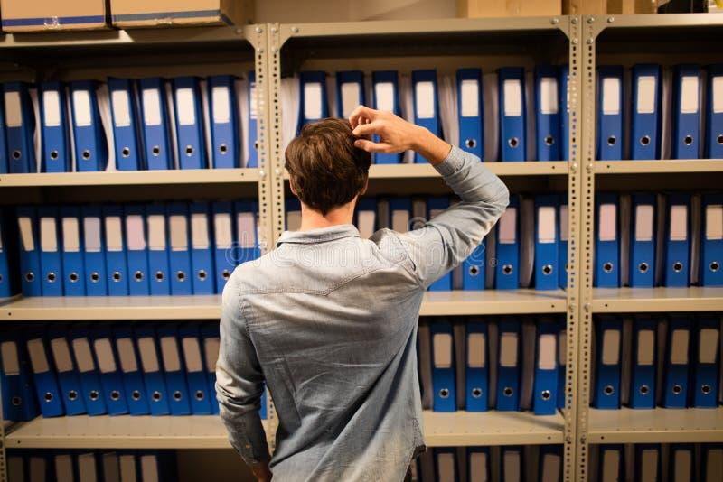 Förvirrad affärsman som söker för mappar på kabinettet i lagringsrum royaltyfri fotografi