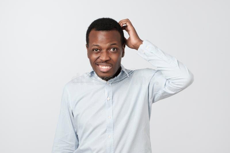 Förvirrad afrikansk man som skrapar huvudet, medan se kameran och stå över grå bakgrund royaltyfri fotografi