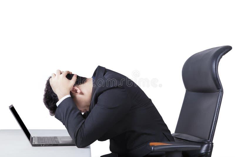 Förvirrad arbetare med bärbara datorn på tabellen royaltyfri fotografi