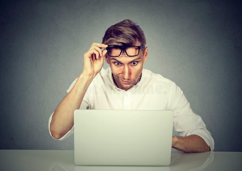 Förvirrad chockad man som ser hans bärbar dator arkivbild