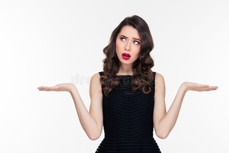 Förvirrad fundersam lockig hållande copyspace för den unga kvinnan på båda gömma i handflatan royaltyfri fotografi
