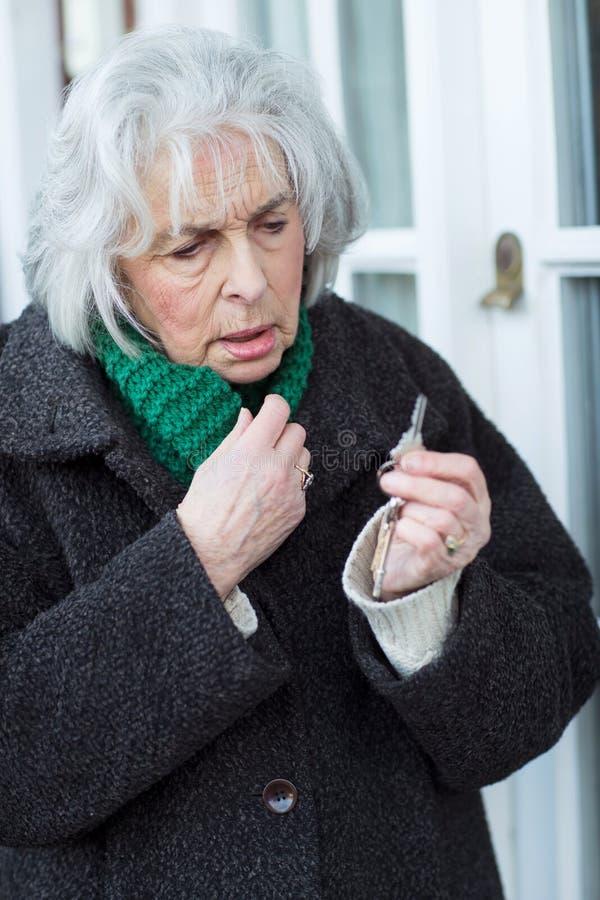 Förvirrad hög kvinna som försöker att finna dörrtangent royaltyfri fotografi