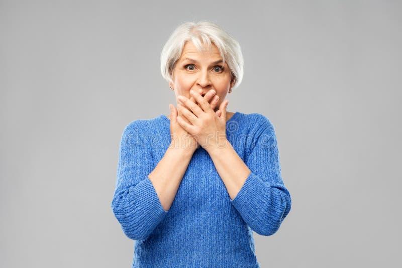 Förvirrad hög kvinna som täcker hennes mun vid händer arkivbilder