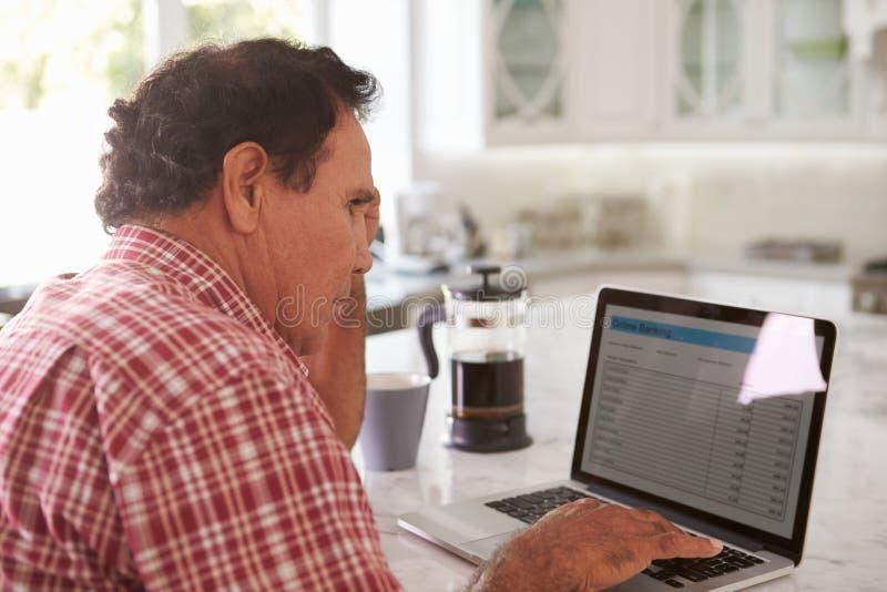 Förvirrad hög latinamerikansk man som hemma sitter genom att använda bärbara datorn arkivbild