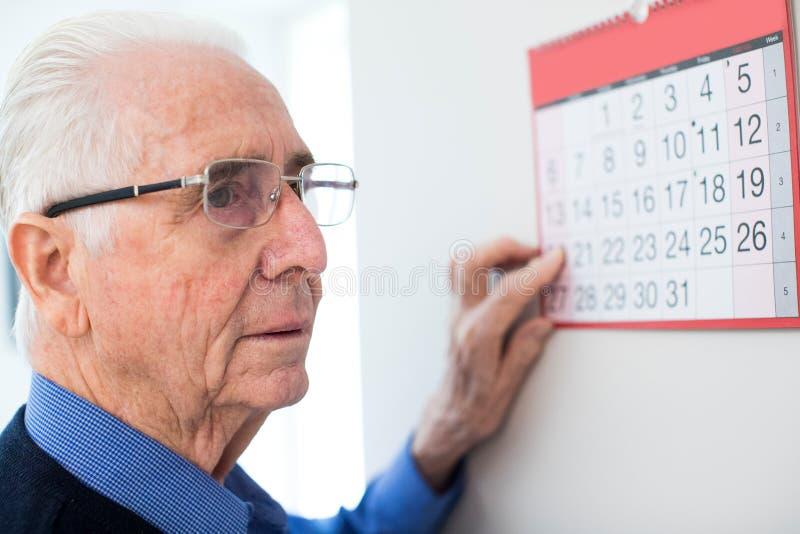 Förvirrad hög man med demens som ser väggkalendern royaltyfri fotografi