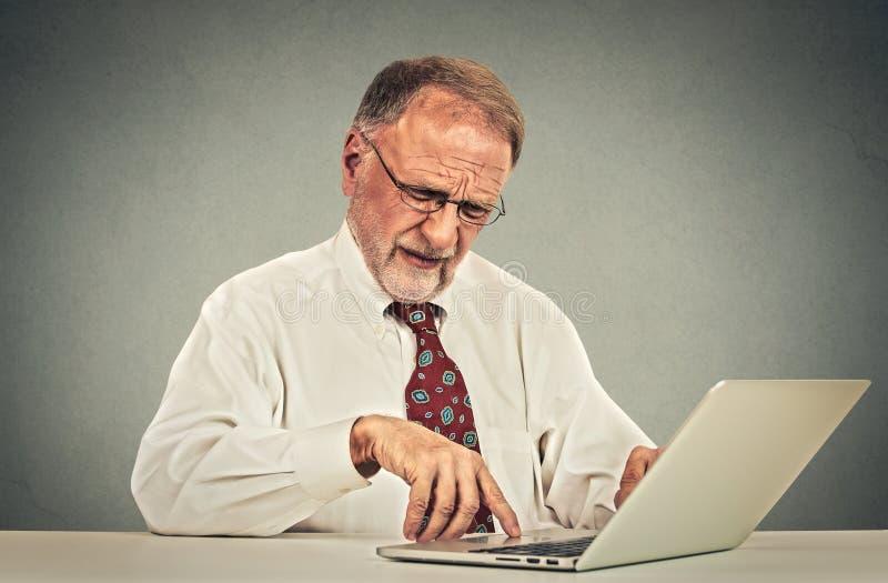 Förvirrad hög man som arbetar på bärbar datordatoren royaltyfri bild