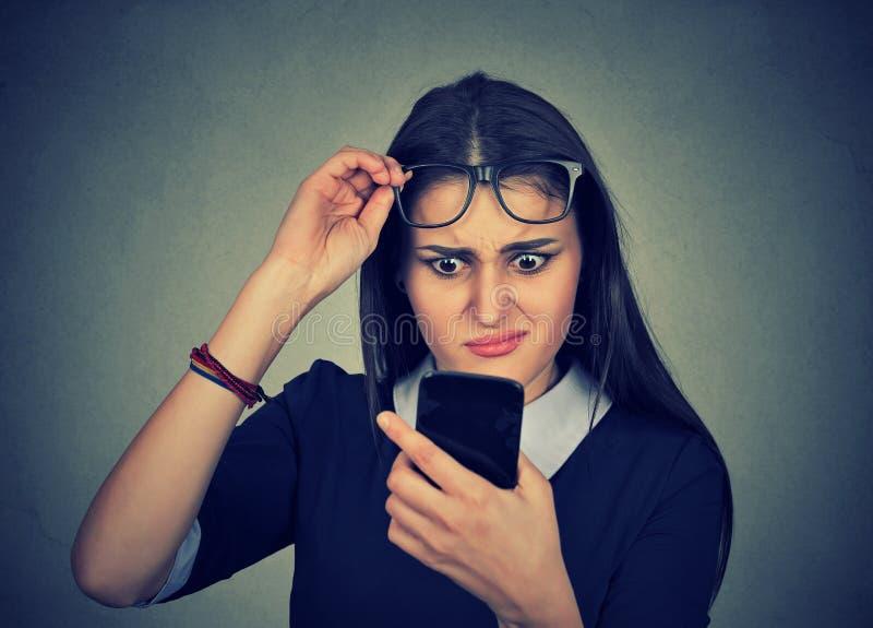 Förvirrad kvinna med exponeringsglas som har problem som ser mobiltelefonen royaltyfri foto
