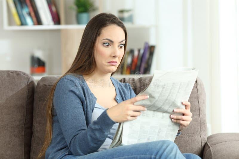 Förvirrad kvinna som läser en tidning på en soffa royaltyfria bilder